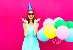 Sorprenden a la mujer joven sonriente feliz en un casquillo del cumpleaños con los globos coloridos de un aire sobre rosa Imágenes de archivo libres de regalías