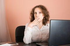 Sorprendido/chocó a la mujer que se sentaba en oficina y que usaba el ordenador portátil Imagenes de archivo