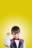 Sorprendido señalando al niño pequeño aislado sobre fondo amarillo fotografía de archivo