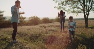 Sorprendiendo gastando los miembros de la familia del tiempo juntos, dos niños pequeños y a padres en la hermosa vista de la natu almacen de video