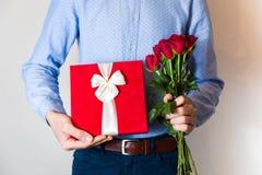 Sorpresa de día de San Valentín, amor, hombre hermoso que sostiene el regalo romántico y el ramo de las rosas rojas imágenes de archivo libres de regalías