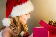 Sorpresa de la mujer al abrir el regalo de la Navidad Foto de archivo