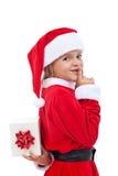 Sorpresa de la Navidad con la niña vestida como Papá Noel Imagen de archivo