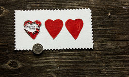 Sorpresa de tres corazones en un fondo de madera el día del ` s de la tarjeta del día de San Valentín Fotos de archivo libres de regalías