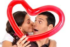 Sorpresa del corazón del globo de los pares que se besa jovenes Foto de archivo libre de regalías