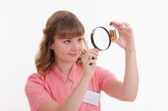 Sorpresa del farmacista che considera liquido tramite una lente d'ingrandimento Fotografia Stock