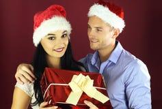 Sorpresa del hombre joven su novia con un presente para la Navidad fotografía de archivo