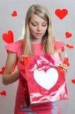 Sorpresa del ` s de la tarjeta del día de San Valentín, muchacha con el bolso del regalo foto de archivo libre de regalías