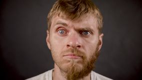 Sorpresa expresa masculina del inconformista barbudo hermoso en el estudio negro metrajes
