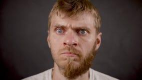 Sorpresa expresa masculina del inconformista barbudo hermoso en el estudio negro almacen de metraje de vídeo