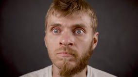 Sorpresa expresa masculina del inconformista barbudo hermoso en el estudio negro almacen de video