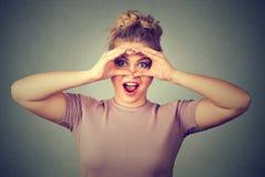 sorpresa La mujer curiosa pasmada que mira a escondidas la mirada a través de los fingeres le gustan los prismáticos Fotografía de archivo libre de regalías