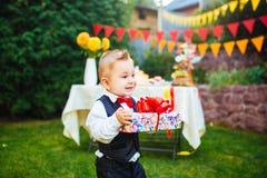 Sorpresa para el cumpleaños el muchacho está sosteniendo una caja con un regalo en la yarda en el fondo de una tabla festiva con  Fotografía de archivo libre de regalías