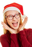 Sorprised young woman at christmas. Surprised young woman at christmas with her hands on her face stock photography