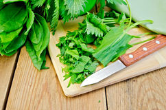 Sorrel and nettles sliced on the board with a knife. Fresh chopped sorrel and nettles on a plate with a knife on a wooden boards background Stock Image