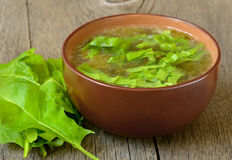 Sorrel soup. In brown bowl on the wooden table Stock Image