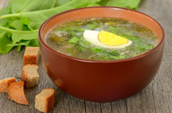 Sorrel soup with egg. In brown bowl on the wooden table Stock Photography