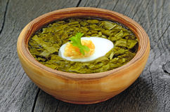 Sorrel soup with egg in brown bowl. On the wooden table Stock Photography