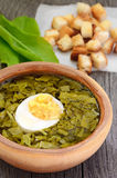Sorrel soup with egg. In brown bowl on the wooden table royalty free stock images