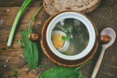 Sorrel soup with egg in a ceramic bowl. Leaves, on a wooden table, rustic style, top view Royalty Free Stock Photo