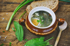 Sorrel soup with egg in a ceramic pot. Leaves, bread on a wooden table, rustic style Royalty Free Stock Photo