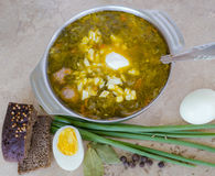 Sorrel soup. Egg, pepper, onion, bread on the table Royalty Free Stock Photography