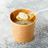 Sorrel soup with egg. Soup from sorrel with quail eggs in a cardboard cup on a gray background. Healthy food delivery Royalty Free Stock Image