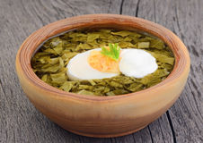 Sorrel soup with egg and sour cream. In brown bowl on the wooden table Stock Photo