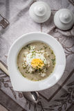 Sorrel soup with egg in white bowl. Stock Photo