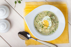 Sorrel soup with egg in white bowl. Homemade sorrel soup with egg and rice in a bowl. Top view Stock Images