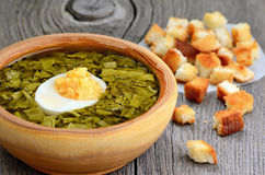 Sorrel soup with egg in wooden bowl. Sorrel soup with egg in bowl on wooden table Stock Photo
