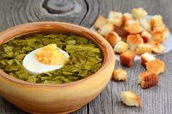 Sorrel soup with egg in wooden bowl. Sorrel soup with egg in bowl on wooden table stock photo