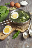 Sorrel soup with egg. On wooden table Stock Photo