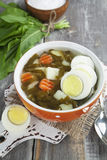 Sorrel soup with eggs. In the ceramic pot on the wooden table Royalty Free Stock Photography