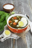 Sorrel soup with eggs. In the ceramic pot on the wooden table Stock Photo