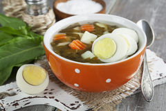 Sorrel soup with eggs. In the ceramic pot on the wooden table Stock Images