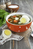 Sorrel soup with eggs. In the ceramic pot on the wooden table Stock Photography