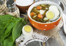 Sorrel soup with eggs. In the ceramic pot on the wooden table Royalty Free Stock Image
