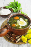 Sorrel soup with eggs. In the ceramic pot on the wooden table Royalty Free Stock Photo