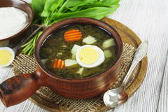Sorrel soup with eggs. In the ceramic pot on the wooden table Stock Image