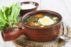Sorrel soup with eggs. In the ceramic pot on the wooden table Stock Photos