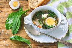 Sorrel soup in a white bowl. Salt, towel, boiled egg, leaves, bread on a wooden table Royalty Free Stock Image
