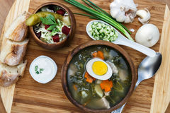 Sorrel soup in wooden bowl with egg and salad. Sorrel soup with egg and salad. Cucumber, onion, garlic and bread on the background Stock Photos