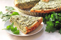 Sorrel tart with goat cheese. With a piece on a plate Royalty Free Stock Images