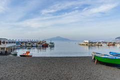 Sorrento, Italy - April 1, 2017: The fisherman boats in beautifu. L sea in south Italian coastal village with the Vesuvio volcano in the background, Spring stock photo