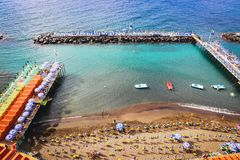 Sorrento summer artificial sand beach with stones of breakwaters on calm blue sea. Italy. Sorrento summer artificial white sand beach with stones of breakwaters stock photography