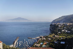 Sorrento and Vesuvius Volcano. A marina, the city of Sorrento at the shore of Napoles Bay with its mediterranean blue waters and Vesuvio Volcano in the horizon Royalty Free Stock Photo