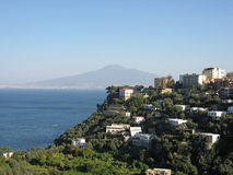Sorrento and Vesuvius Volcano. A hill with typical housing in Sorrento at the shore of Napoles Bay with its mediterranean blue waters and the Vesuvius Volcano at Stock Photography