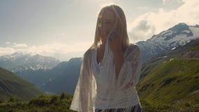 Sorria na cara, vento no cabelo, menina na parte superior do penhasco da montanha Jovens mulheres atrativas de volta à câmera video estoque