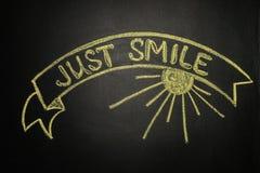Sorrida appena con l'insegna del nastro, scritta con gesso su un blackboar Immagine Stock